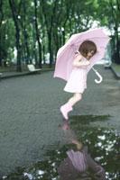 ピンクの傘をさして遊ぶ女の子