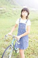 草原で自転車を引く女の子
