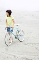 砂浜で自転車を引く女の子