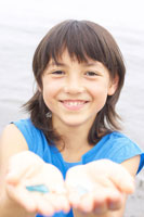 砂浜で石を拾うハーフの女の子 02336002949  写真素材・ストックフォト・画像・イラスト素材 アマナイメージズ