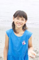 砂浜で石を拾うハーフの女の子