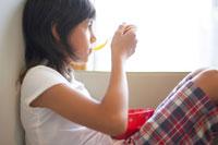 窓辺でシリアルを食べる女の子