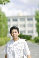 校舎の前に立つ男子中学生