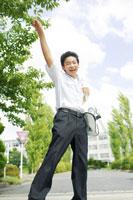 校舎の前で飛ぶ男子中学生
