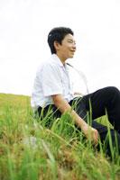 堤防の草むらに座る男子中学生
