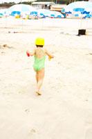 浜辺を走る水着姿の女の子の後姿