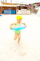 浮き輪を付けて浜辺を走る女の子