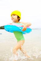 浮き輪を付けて海辺を走る女の子