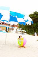 ビーチボールを抱えて浜辺に座る女の子