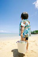 砂浜にバケツを持つて立つ男の子の後ろ姿