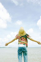 海辺で深呼吸する女性の後ろ姿