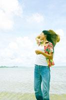 海辺で髪をなびかせる20代女性