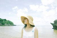 海辺に立つ帽子をかぶった女性