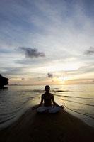 海辺で夕日を背に瞑想する20代女性