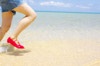 波打ち際を走る女性の足元