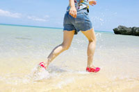 波打ち際を水しぶきをあげて走る女性の足元