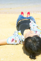 砂浜に手を広げ寝転ぶ女性