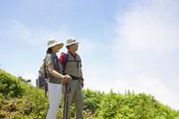 トレッキングで高台から遠方を眺めるシニア夫婦