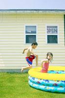 ビニールプールで遊ぶハーフの兄と妹