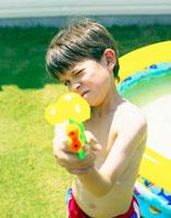 水てっぽうで狙いを付けるハーフの男の子