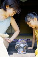 縁側に座り笑顔で金魚を見る母親と女の子