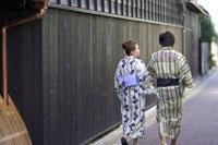 浴衣姿で町並みを歩く女性と男性の後ろ姿