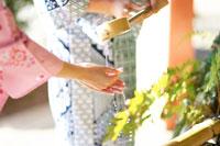 柄杓の水で手を清める浴衣姿の女性の手