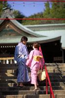 神社の階段を登る浴衣姿の20代女性と男性