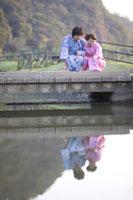 橋の上でしゃがむ浴衣姿の20代女性と男性