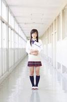 学校の廊下に立つノートを持った女子高校生