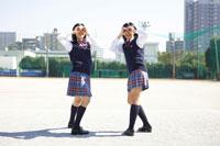 校庭でポーズをとる2人の女子中学生