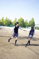 校庭でおどける2人の女子中学生