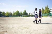 校庭を歩きながら会話する2人の女子中学生