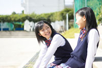 グランドの階段で雑談する2人の女子中学生