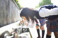 蛇口から水を飲む女子中学生