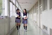 学校の廊下を笑顔で歩く2人の女子中学生