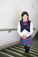階段に立つ笑顔の女子中学生