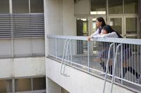 学校の通路から外を見る2人の女子中学生