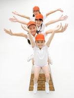 跳び箱の上の体操着の女の子4人