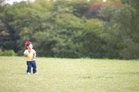 芝生広場に立つ男の子 02336004002| 写真素材・ストックフォト・画像・イラスト素材|アマナイメージズ