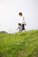草原を歩く男の子とお母さん