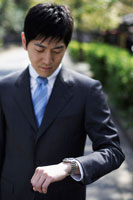 時計を見るスーツ姿の男性