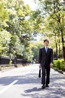 道を歩くスーツ姿の男性