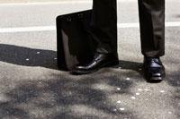 スーツ姿の男性の足元に散る桜の花びら