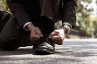 靴の紐を結び直すスーツ姿の男性の足元