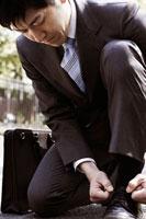 靴の紐を結び直すスーツ姿の男性