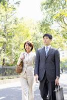 笑顔で会話をするスーツ姿の男性と女性