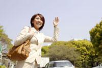 タクシーを止めるスーツ姿の女性