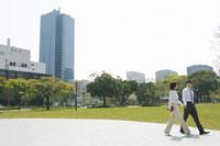 休憩中に公園内を歩くスーツ姿の男性と女性