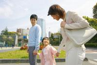 手を繋いで歩く親子3人
